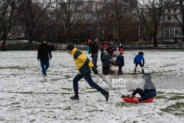 Man pulls a sledge across snow covered ground in a park in Wandsworth in south west London, on 24 January, 2021 in London, England. Snow swept across...