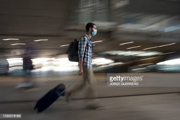 Man pulls a suitcase at Malaga-Costa del Sol Airport on June 7, 2021 in Malaga. - Spain opened its borders to vaccinated travellers from all over the...