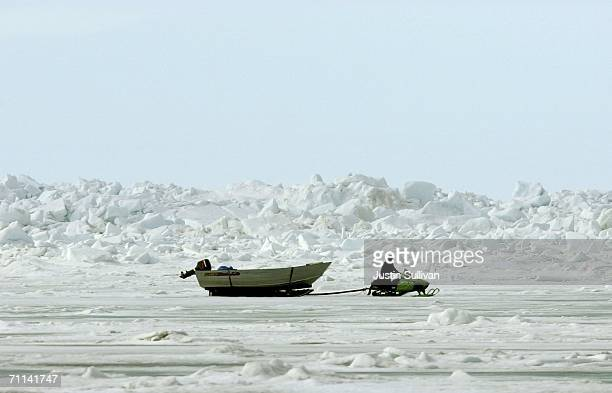 A man pulls a whaler's boat across the frozen Arctic Ocean June 6 2006 in Browerville Alaska Scientists continue to study changes in the Earth's...