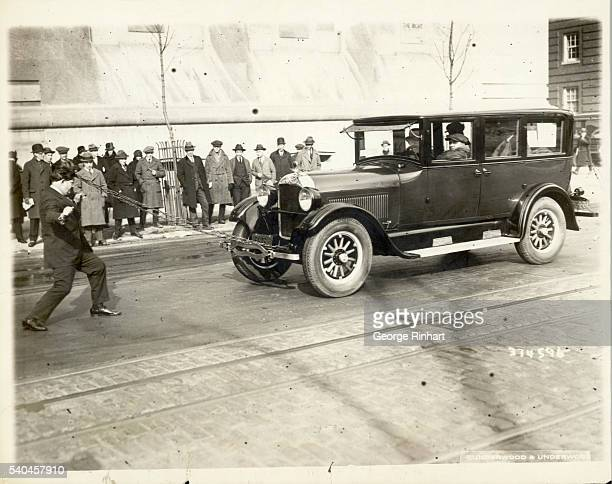 A man pulls an automobile and several passengers by a chain attatched to a lock of his own hair Undated photograph circa 1925