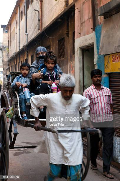 A man pulls an Muslim family through a Calcutta back street in his rickshaw According to the local government the pull rickshaws are in the process...