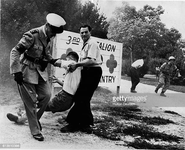 A man pulls another across the ground with the aid of a military policeman during a two hour street battle between Italians and Yugoslavs in Gorizia...