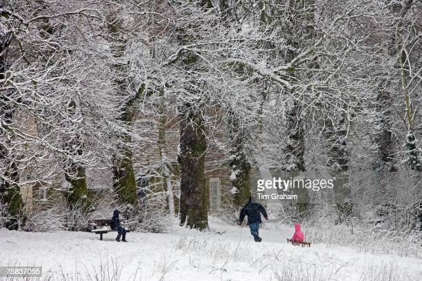 Man pulls child on a toboggan on winter's day on snowcovered Hampstead Heath London United Kingdom