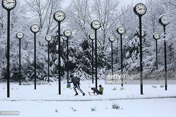 TOPSHOT A man pulls children on a sledge through fresh snow fallen on the clock park a sculpture by artist Klaus Rinke made of 24 station clocks in...