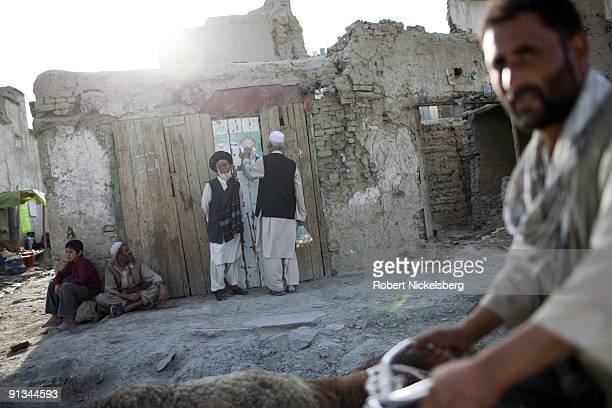 A man pulls down a political campaign poster while a flock of sheep moves through a Jangalak neighborhood street during the month of Ramadan in Kabul...