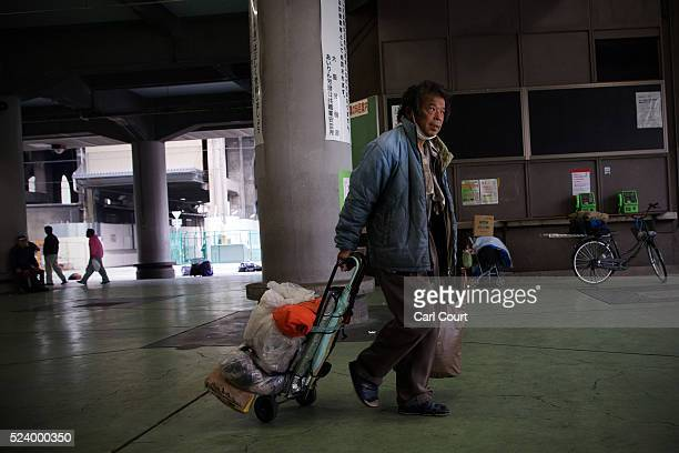 A man pulls his belongings through the slum area of Kamagasaki on April 23 2016 in Osaka Japan Kamagasaki a district in Japan's second largest city...