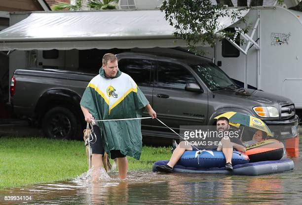 A man pulls his friends on a raft on flooded Apple Street in Pearland on August 27 2017 as the US fourth city city battles with tropical storm Harvey...