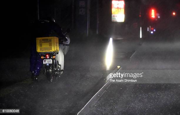 A man pulls his motorbike in the heavy rain as Typhoon Malakas approaches on September 19 2016 in Miyazaki Japan Japan could suffer from a record...