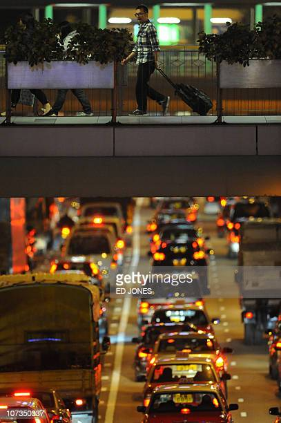 A man pulls his suitcase over a bridge above traffic in Hong Kong on December 4 2010 About 25 percent of Hong Kong's population wants to leave the...
