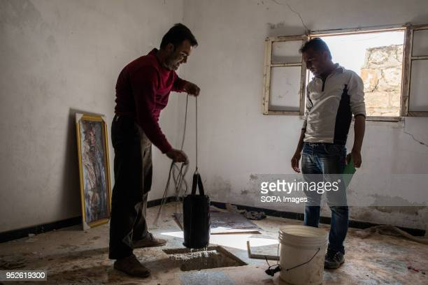 A man pulls up water from a well discovered beneath an empty home in Mahatah He resettled his family in this house An estimated 400000 refugees...