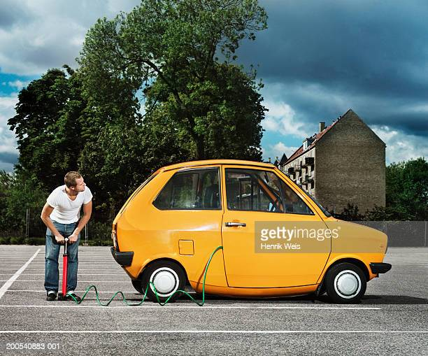 man pumping yellow car in car park - air pump stock photos and pictures