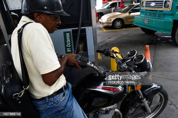 A man pumps fuel into his motorbike at a gas station in Caracas on July 30 2018 Venezuelan President Nicolas Maduro announced fuel price regulations...