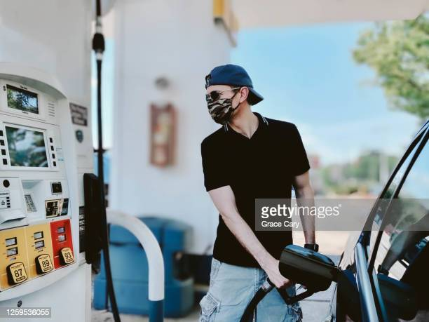 man pumps gas wearing protective face mask - service stock pictures, royalty-free photos & images