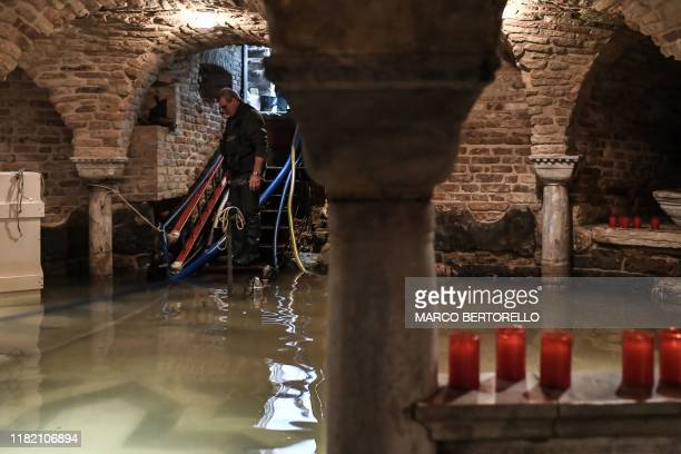 "Man pumps out water from the flooded crypt of St. Mark's Basilica after an exceptional overnight ""Alta Acqua"" high tide water level, on November 13,..."
