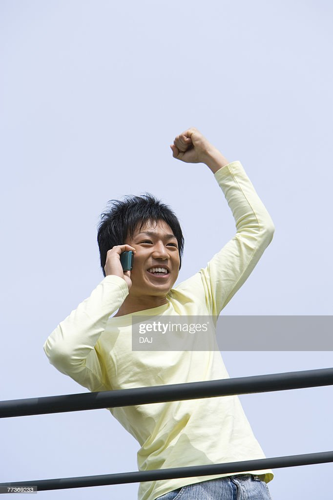 Man punching air and using mobile phone under the blue sky, front view, blue background, Japan : Photo
