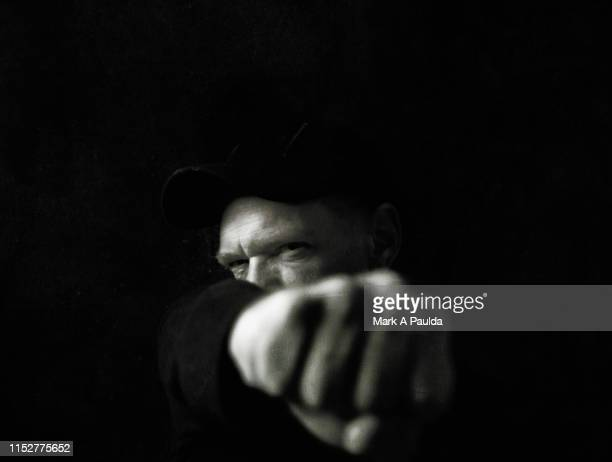 man punching his fist into the foreground - furioso foto e immagini stock