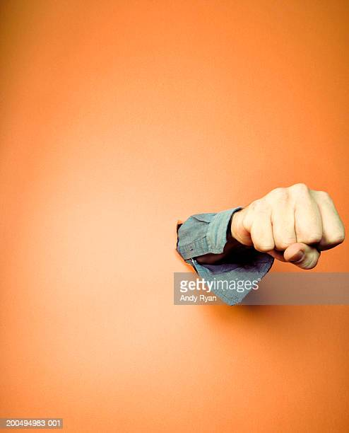 Man punching hole in orange wall, close-up of fist