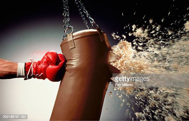 man punching punch bag and stuffing exploding from bag - punching stock pictures, royalty-free photos & images