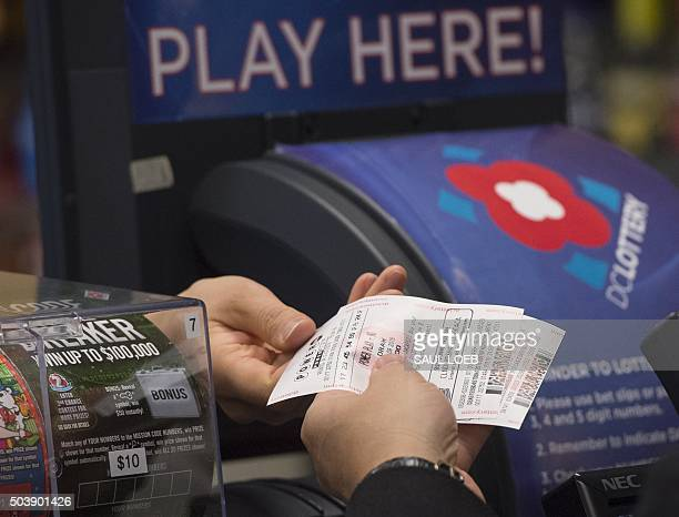 A man purchases a Powerball lottery ticket at a convenience store in Washington DC January 7 2016 Lottery officials predict Saturday's jackpot will...