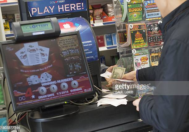 A man purchases a Powerball lottery ticket at a liquor store in Washington DC January 4 2016 Lottery officials predict the January 6 jackpot will...