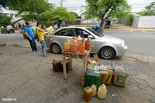 A man purchases black market gasoline on the street in Cucuta Colombia on Tuesday Feb 24 2015 Colombians in Cucuta on the border with Venezuela dine...
