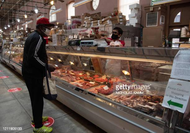 Man purchases meat at Eastern Market in Washington, DC, on May 5, 2020. - US slaughterhouses have emerged as COVID-19 outbreak hotspots in several...