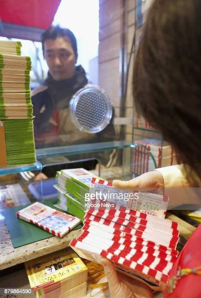 A man purchases yearend 'Jumbo' lottery tickets at a lottery booth in Tokyo's Ginza district on Nov 27 2017 The 300yen tickets which give purchasers...