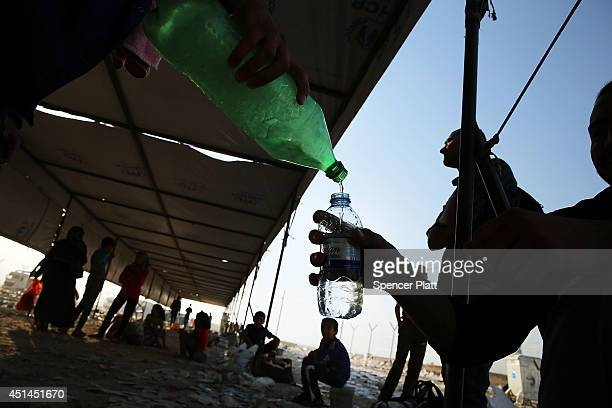 A man purs water for a person at a displacement camp for those caughtup in the fighting in and around the city of Mosul on June 28 2014 in Khazair...