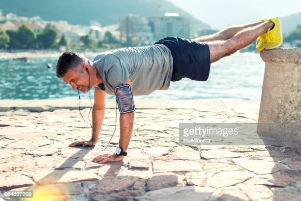Man push up workout outside by the sea