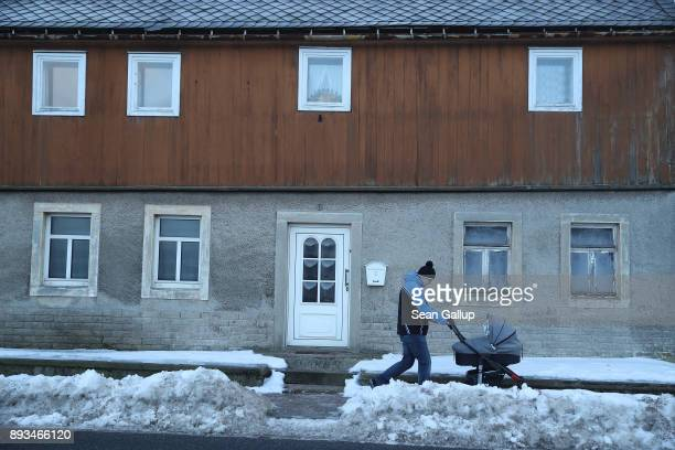 A man pushes a baby pram in the town center on December 13 2017 in the former mining town of Altenberg Germany Altenberg will potentially experience...