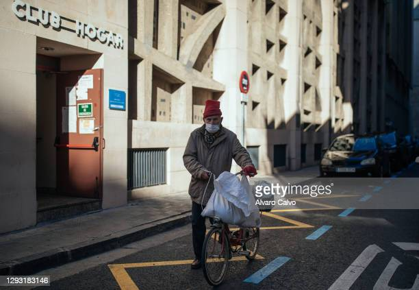 Man pushes a bicycle after picking up a tupperware with food from the soup kitchen of Carmen parish on Christmas Day, due to the restrictions of the...