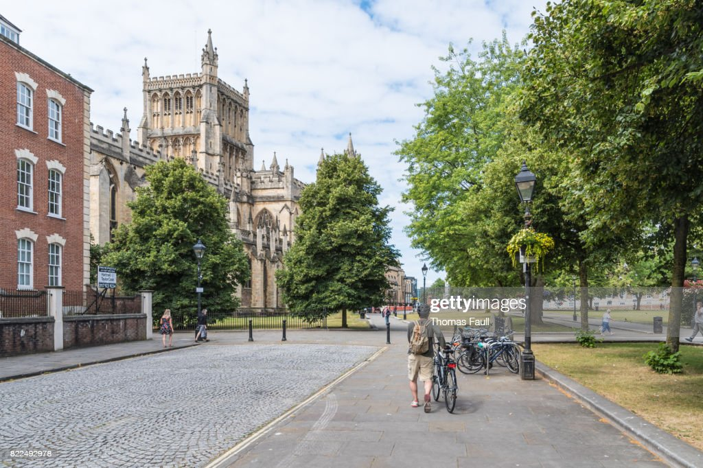 Man pushes a bicycle along a road near Bristol Cathedral : Stock Photo