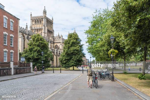 man pushes a bicycle along a road near bristol cathedral - bristol england stock pictures, royalty-free photos & images