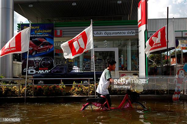 A man pushes a bicycle down a flooded street past a Isuzu Motors Ltd car dealership in Bangkok Thailand on Wednesday Oct 26 2011 Thai Prime Minister...