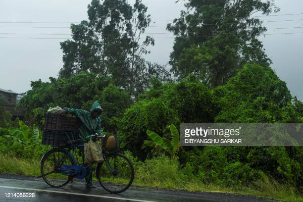 A man pushes a bicycle loaded with vegetable under the rain ahead of the expected landfall of cyclone Amphan in Midnapore West Bengal on May 20 2020...