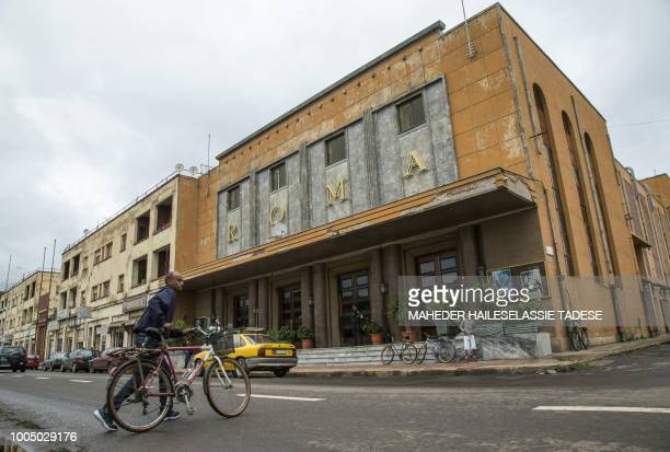 Man pushes a bicycle on July 20, 2018 in front of an art-deco cinema Roma in the Eritrean capital Asmara, an UNESCO World Heritage Site renowned for...