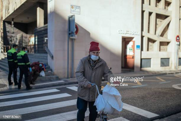 Man pushes a bike after picking up a tupperware with food from the soup kitchen of Carmen parish on Christmas Day, due to the restrictions of the...