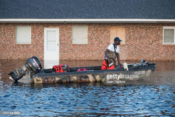 Man pushes a boat in floodwaters from the Waccamaw River caused by Hurricane Florence on September 26, 2018 in Bucksport, South Carolina. Nearly two...