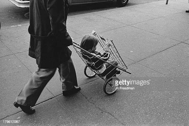 A man pushes a boy in a shopping cart New York City 1982