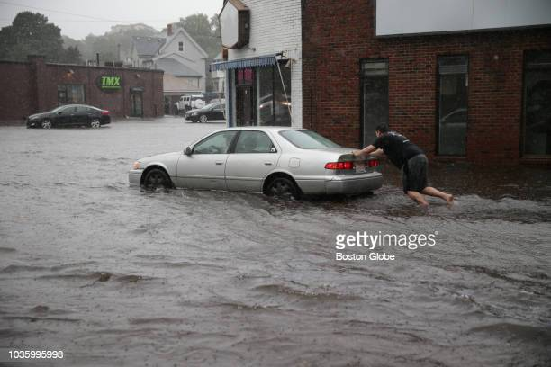 Man pushes a car on Independence Avenue in Quincy, MA after the street was flooded by heavy rain on Sep. 18, 2018. The storm containing the remnants...
