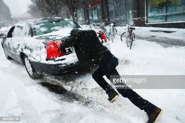 A man pushes a car stuck in the snow on February 9 2017 in the Brooklyn borough of New York City A major winter storm warning is forecast from...