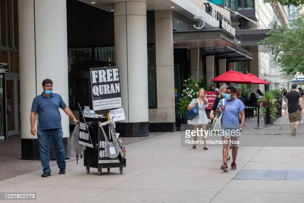 A man pushes a car with a sign reading 'Free Quran' during the Coronavirus pandemic The image is taken in the downtown district