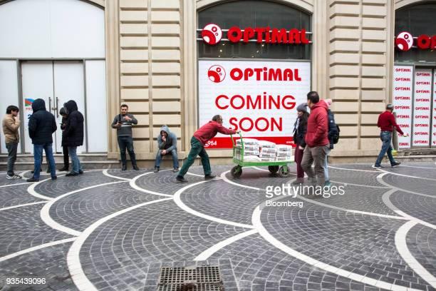 A man pushes a cart of construction materials past an Optical Electronics store in Baku Azerbaijan on Friday March 16 2018 Azerbaijan's economy...