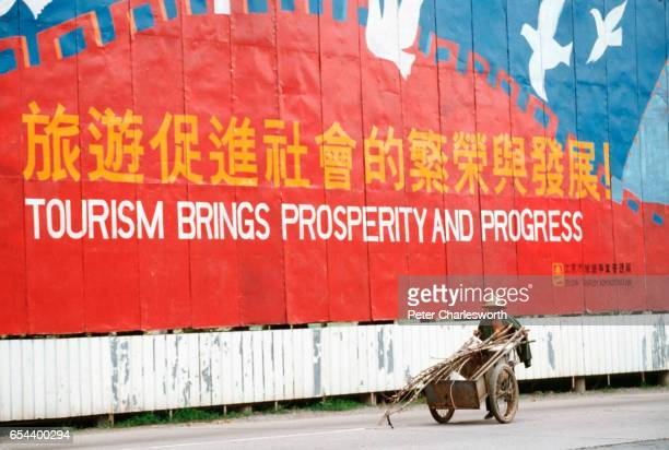 A man pushes a cart past a huge advertising billboard hoping to promote tourism in China just a few days after Communist Government troops brutally...