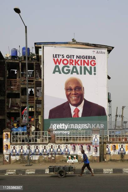 A man pushes a cart past a poster of Atiku Abubakar candidate of the main opposition Peoples Democratic Party in Lagos Nigeria on Saturday Feb 16...