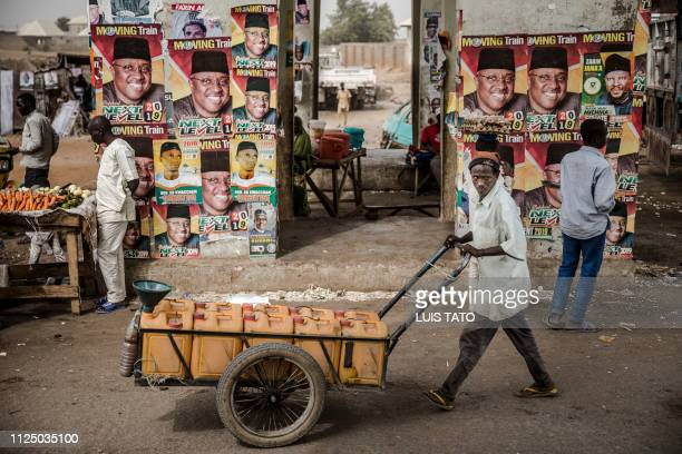 TOPSHOT A man pushes a cart past electoral posters in the Nigerian city of Mubi Adamawa State on February 15 on the eve of the country's presidential...