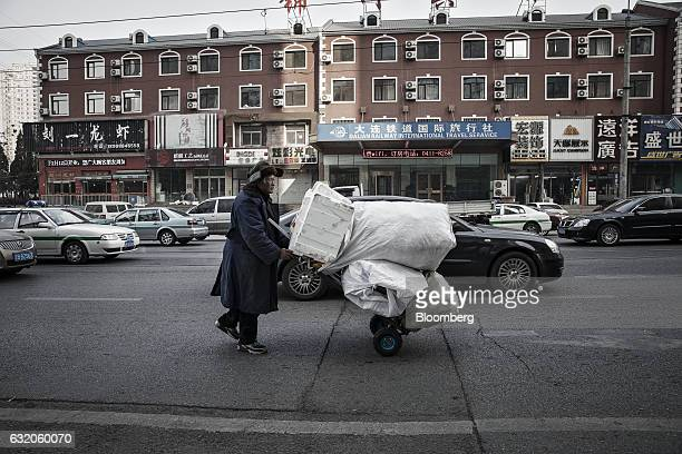 A man pushes a cart piled with scrap materials down a street in Dalian China on Wednesday Jan 18 2017 Contrasting fortunes in Dalian illustrate...