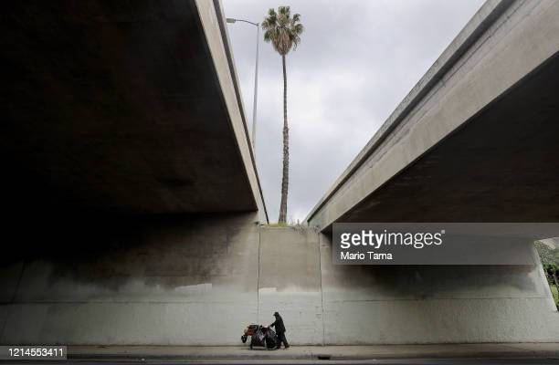 A man pushes a cart with items to recycle beneath an overpass in an unusually quiet downtown as the coronavirus pandemic continues on March 24 2020...