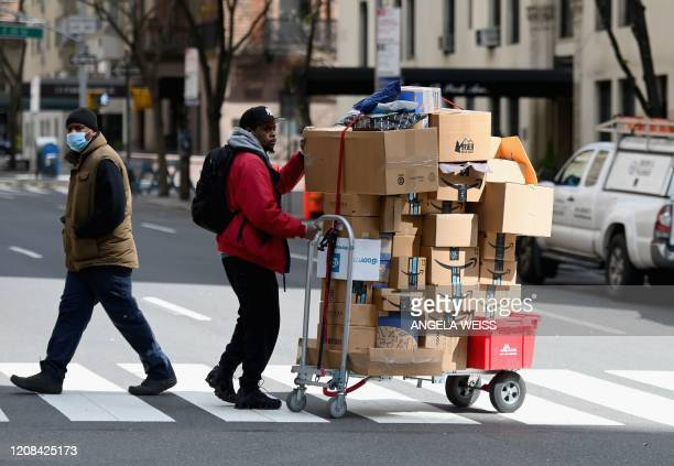 Man pushes a cart with packages on March 27, 2020 in New York City. - The new coronavirus isn't picky about who it infects -- so why does data...