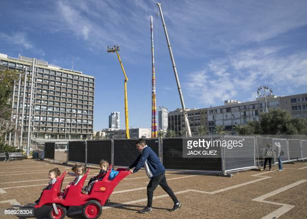 A man pushes a child stroller as he passes by a LEGO tower under construction in Tel Aviv's Rabin Square on December 27 as the city attempts to break...